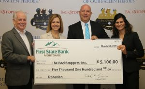 Photo of First State Bank executives presenting a check to The BackStoppers