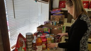 Photo of First State Bank team member sorting canned food collected by employees